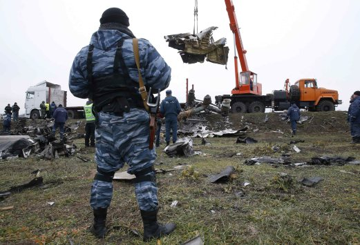 A pro-Russian separatist watches as a crane carries wreckage of the Malaysia Airlines Boeing 777 plane at the site of the plane crash near the village of Hrabove in Donetsk region