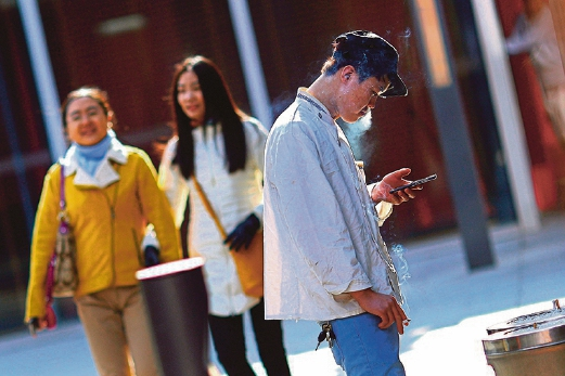 A man looks at his mobile phone as he smokes at Sanlitun Village, a shopping area in Beijing